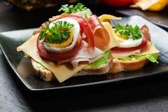 Sanduíche delicioso com presunto de prosciutto, queijo, tomate e ovo imagem de stock