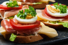 Sanduíche delicioso com presunto de prosciutto, queijo, tomate e ovo fotografia de stock