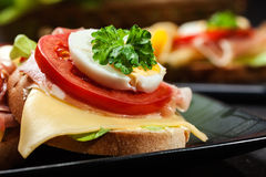 Sanduíche delicioso com presunto de prosciutto, queijo, tomate e ovo imagens de stock royalty free