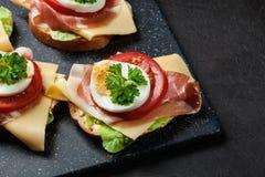 Sanduíche delicioso com presunto de prosciutto, queijo, tomate e ovo foto de stock royalty free