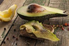 Sanduíche do abacate com o limão na placa de madeira Fotografia de Stock