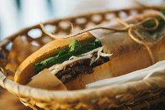 Sanduíche do close-up com a carne, o pepino e os verdes envolvidos no papel e prendidos com mentiras da corda na cesta na tabela Foto de Stock