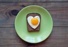 Sanduíche do pão de centeio com os ovos mexidos sob a forma do coração Imagens de Stock Royalty Free