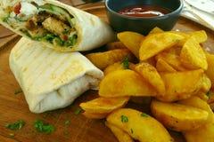 Sanduíche do queijo fresco e do envoltório da galinha com batatas em uma placa de corte de madeira imagem de stock