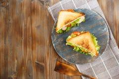 Sanduíche dois saboroso com galinha, tomates, alface, queijo em uma placa de madeira em um fundo escuro imagens de stock royalty free