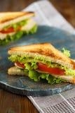 Sanduíche dois saboroso com galinha, tomates, alface, queijo em uma placa de madeira em um fundo escuro imagens de stock