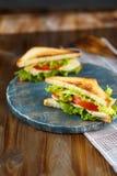 Sanduíche dois saboroso com galinha, tomates, alface, queijo em uma placa de madeira em um fundo escuro imagem de stock