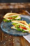 Sanduíche dois saboroso com galinha, tomates, alface, queijo em uma placa de madeira em um fundo escuro fotografia de stock