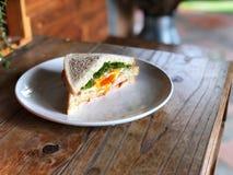 Sanduíche fresco no prato branco na tabela de madeira com luz natural, café da manhã delicioso fotos de stock royalty free