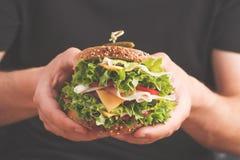 Sanduíche grande com carne, queijo e os legumes frescos na mão masculina imagens de stock