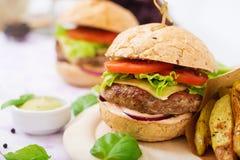 Sanduíche grande - Hamburger com o hamburguer suculento da carne, o queijo, o tomate, e a cebola vermelha Fotos de Stock