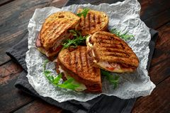 Sanduíche grelhado com peru, bacon, tomate e queijo no fundo de madeira rústico imagem de stock