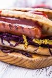 Sanduíche grelhado da salsicha com salada de repolho doce e mostarda marcante Fotografia de Stock
