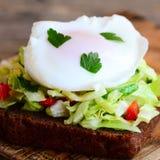 Sanduíche home do brinde do ovo escalfado Um ovo escalfado em uma fatia do pão de centeio com salada de repolho fresca, pepino, p foto de stock royalty free