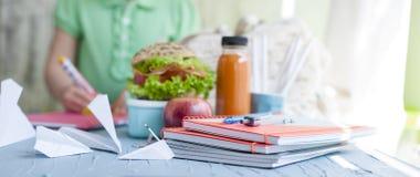 Sanduíche para o almoço escolar e o suco, almoço saudável Livros de escola na tabela e na estudante Copie o espaço imagens de stock royalty free