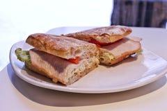 Sanduíche quente delicioso com peru, tomates, alface, cortada, em uma placa imagens de stock