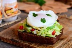 Sanduíche vegetal da salada e do ovo escalfado Ovo escalfado na fatia do pão de centeio com couve fresca, pepino, pimenta vermelh fotos de stock royalty free