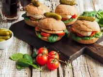 Sanduíches caseiros com galinha, os tomates e espinafres grelhados em um bolo rústico Imagem de Stock