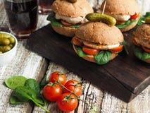Sanduíches caseiros com galinha, os tomates e espinafres grelhados em um bolo rústico Foto de Stock Royalty Free
