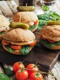 Sanduíches caseiros com galinha, os tomates e espinafres grelhados em um bolo rústico Imagem de Stock Royalty Free