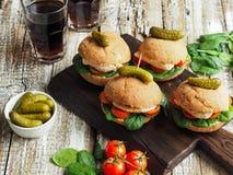 Sanduíches caseiros com galinha, os tomates e espinafres grelhados em um bolo rústico Imagens de Stock