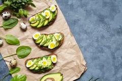 Sanduíches caseiros saudáveis do brinde do abacate com guacamole, abacates da fatia, espinafres, rúcula e ovos de codorniz no per Fotografia de Stock Royalty Free