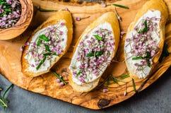 Sanduíches com as flores comestíveis do queijo creme e do alho, placa verde-oliva Fotografia de Stock