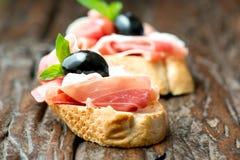 Sanduíches com azeitona do prosciutto na tabela velha de madeira horizontal Imagem de Stock Royalty Free