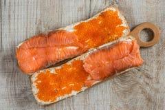 Sanduíches com caviar e os salmões vermelhos no fundo de madeira Foto de Stock Royalty Free