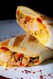 Sanduíches com a faixa da galinha, os legumes frescos e as ervas grelhados na placa cerâmica branca Foto de Stock
