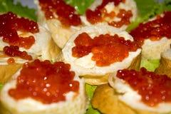 Sanduíches com fundo vermelho do fim do caviar fotos de stock royalty free