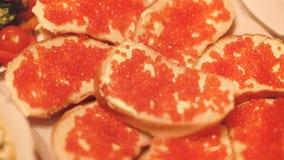 Sanduíches com manteiga e o caviar vermelho da espécie salmon salmon dos peixes filme