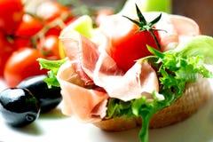 Sanduíches com o prosciutto na placa com tomate fotografia de stock