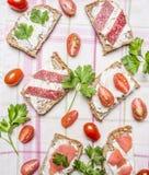 Sanduíches com opinião superior do fundo rústico de madeira dos tomates de cereja, da salsa, dos salmões e do salame Fotos de Stock