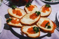 Sanduíches com os peixes do caviar e manteiga e salsa vermelhos Foto de Stock