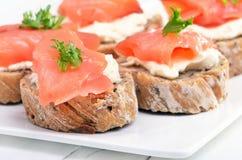 Sanduíches com os salmões na placa branca Imagens de Stock