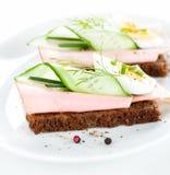 Sanduíches com ovo, presunto, pepino e cebolinha na placa branca Imagens de Stock Royalty Free