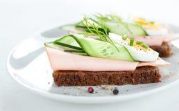Sanduíches com ovo, presunto, pepino e cebolinha na placa branca Fotos de Stock