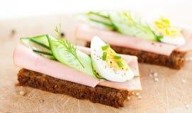 Sanduíches com ovo, presunto, pepino e cebolinha na placa de madeira Fotografia de Stock Royalty Free