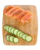 sanduíches com pão, os peixes frescos e os pepinos cortados com as especiarias na bandeja de madeira isolada no fundo branco imagens de stock royalty free