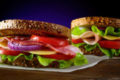Sanduíches com presunto, bacon, tomate, pepino, queijo, e ervas no fundo escuro Foto de Stock Royalty Free