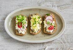 Sanduíches com queijo creme, ovo, rabanete, tomates, pepino e pão inteiro da grão na placa oval Fotografia de Stock Royalty Free