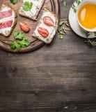 Sanduíches com queijo de coalho com salsa, tomates de cereja e salmões em uma placa de corte e um chá do copo com beira do tomilh Foto de Stock Royalty Free