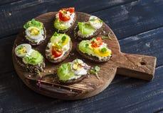 Sanduíches com queijo macio, ovos de codorniz, tomates de cereja e aipo Petisco ou café da manhã saudável delicioso Fotos de Stock Royalty Free