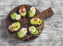 Sanduíches com queijo macio, ovos de codorniz, tomates de cereja e aipo Petisco ou café da manhã saudável delicioso Fotos de Stock