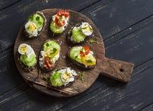 Sanduíches com queijo macio, ovos de codorniz, tomates de cereja e aipo Petisco ou café da manhã saudável delicioso Imagens de Stock