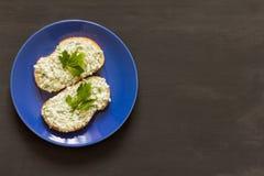Sanduíches com requeijão e ervas em uma placa azul foto de stock