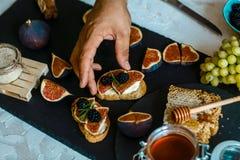 Sanduíches com ricota, os figos frescos, as nozes e o mel na placa rústica do xisto Vista superior Café da manhã, foto do aliment fotos de stock