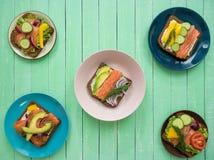 Sanduíches com salmões, pão preto e vegetais nas placas na tabela Foto de Stock