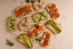 Sanduíches com salmões, pepino, tomates, abacates e verdes, vegetal cortado foto de stock royalty free